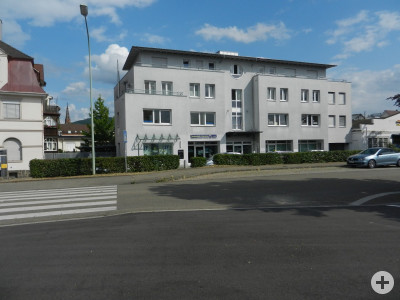 Das weiße Gebäude mit vier Stockwerken, im Vordergrund die Güterstraße, dazwischen ein Grünstreifen mit niedrig geschnittenen Büschen.