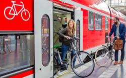 Frau steigt mit Fahrrad aus dem Zug
