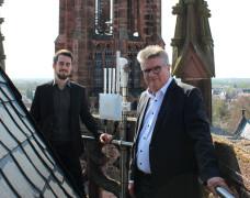 Eduard Itrich und Hubert Schnurr präsentieren auf dem Rathaus-Turm das erste Gateway, das die Stadt in Betrieb genommen hat.