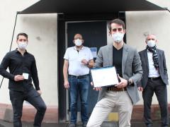 Eduard Idrich zeigt auf dem Tablett die neue Internetseite. Er steht mit Bürgermeister Wolfgang Jokerst und zwei weiteren Männer vor dem Eingang zum Friedrichsbau