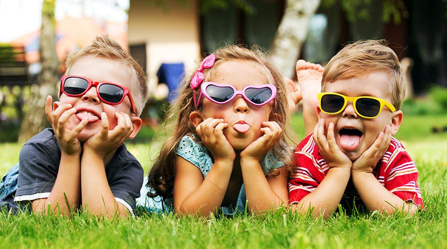 Drei Kinder auf dem Bauch liegend mit Sonnenbrillen