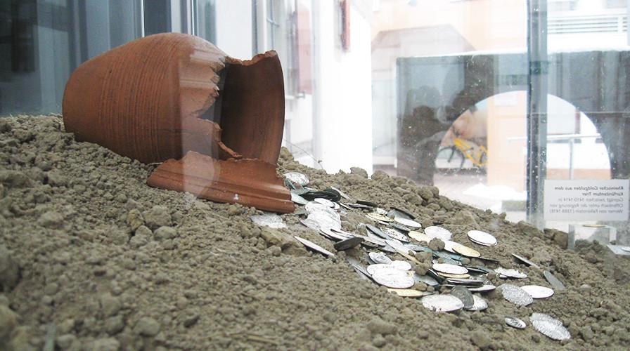 Vitrine mit zerbrochener Vase und Münzen im Stadtmuseum