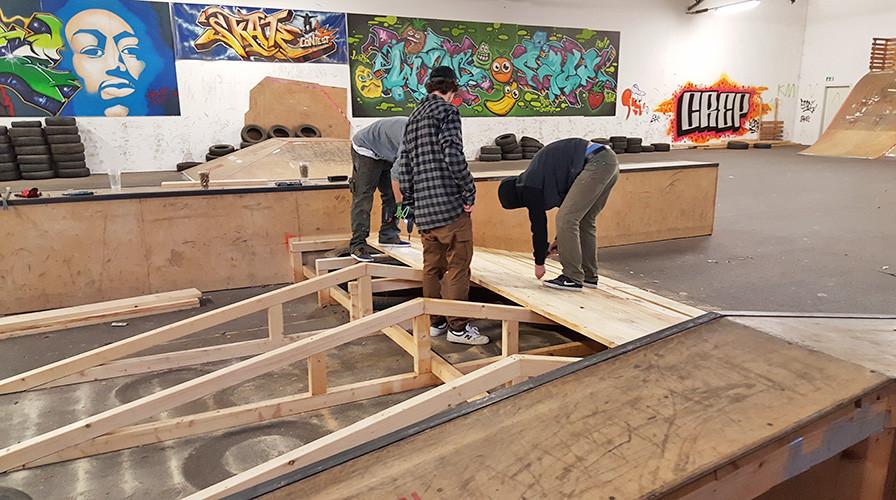 Jugendliche Skater beim Bau einer Pyramidenbank