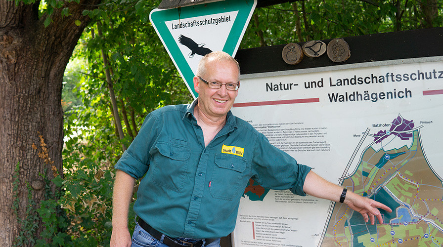 Joachim Doll zeigt auf Karte mit Natur- und Landschaftsschutzgebiet Waldhägenich