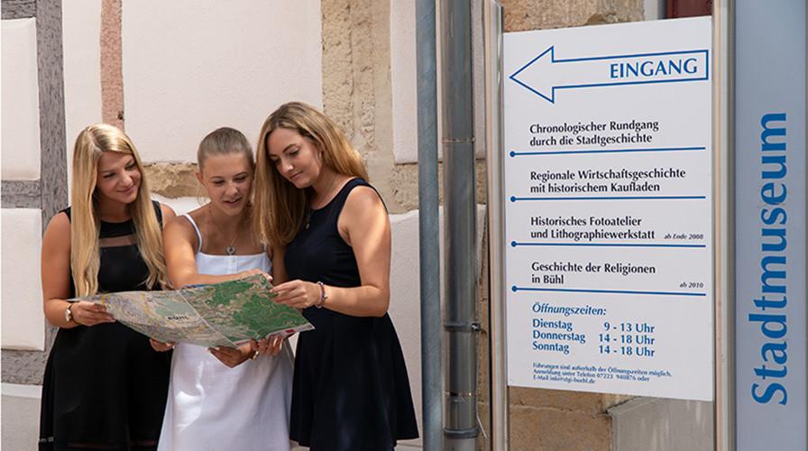 Drei Frauen mit Stadtplan in der Hand vor dem Stadtmuseum
