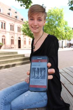 """Frau zeigt Jugendbeteiligungs-App """"JuiB"""" auf dem Handy"""