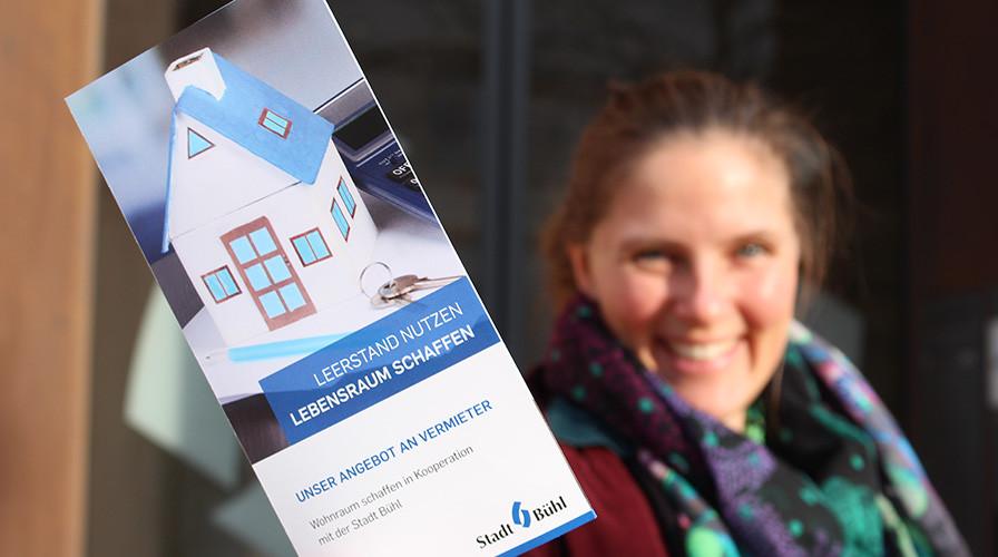 Frau zeigt Flyer zum Programm Wohnraum