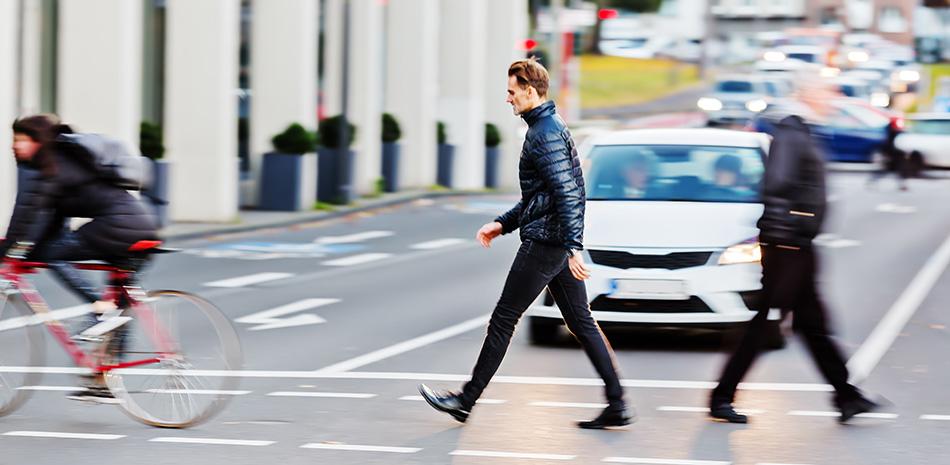 Fahrradfahrer, Fußgänger und Auto im Straßenverkehr