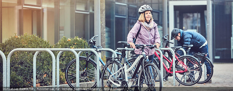 Frau mit Fahrradhelm schiebt Fahrrad