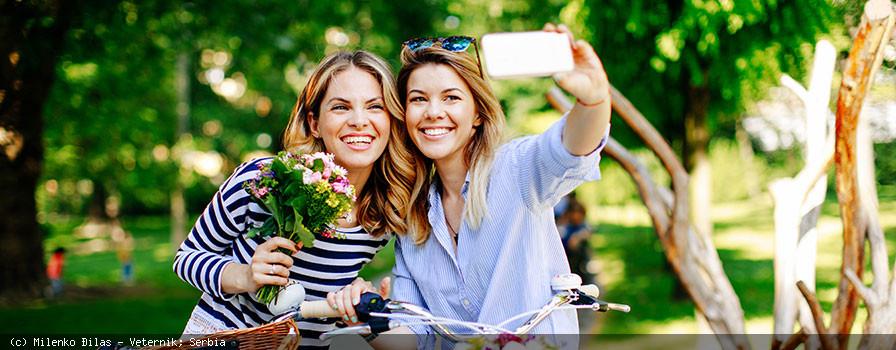 Frauen machen eine Selfie mit ihrem Fahrrad und den Einkäufen