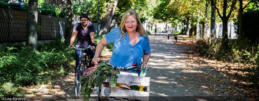 Frau mit Fahrrad und Einkaufskorb